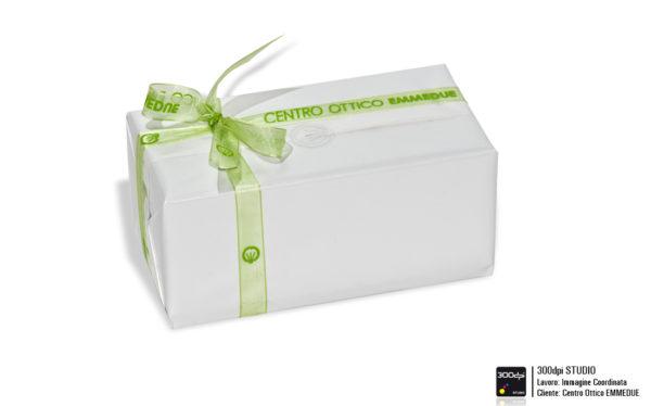 Esempio di pacco regalo con carta plastificata semilucida, nastro con logo del centro ottico e adesivo di chiusura trasparente con stampa in argento della parte iconografica del marchio.